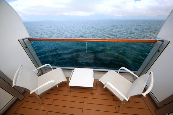 balcony with chairs table with view on sea on ship