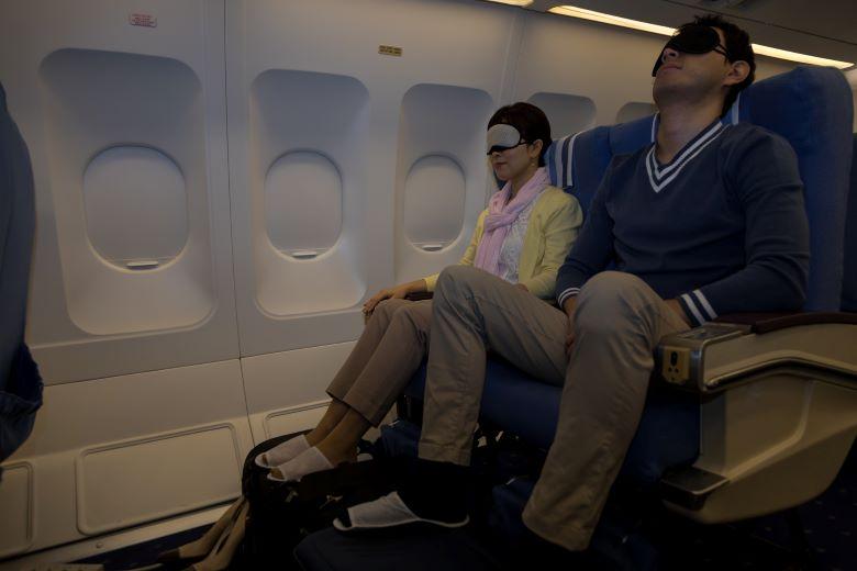 飛行機で寝る夫婦